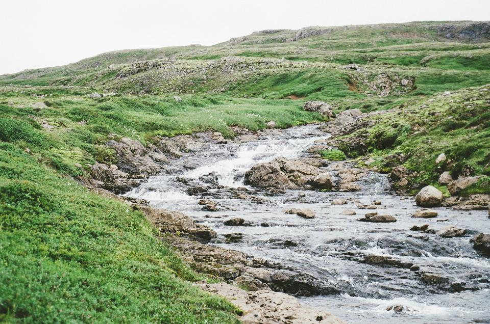 water stream rocks grass fields hills green river