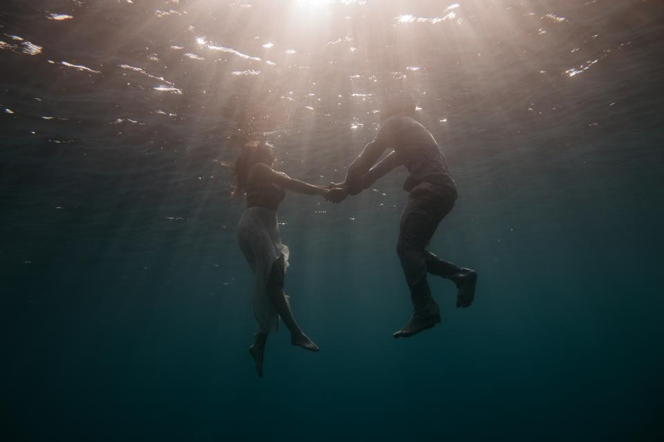people man woman holding hands swimming underwater sea ocean water lights