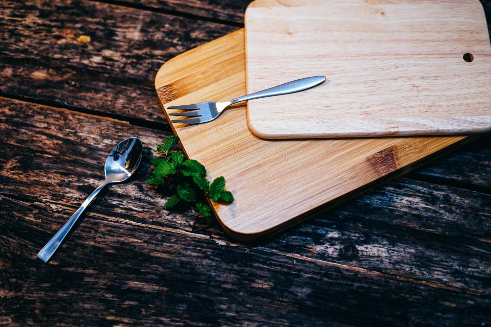 wooden table wood chopping board spoon fork green leaf outdoor