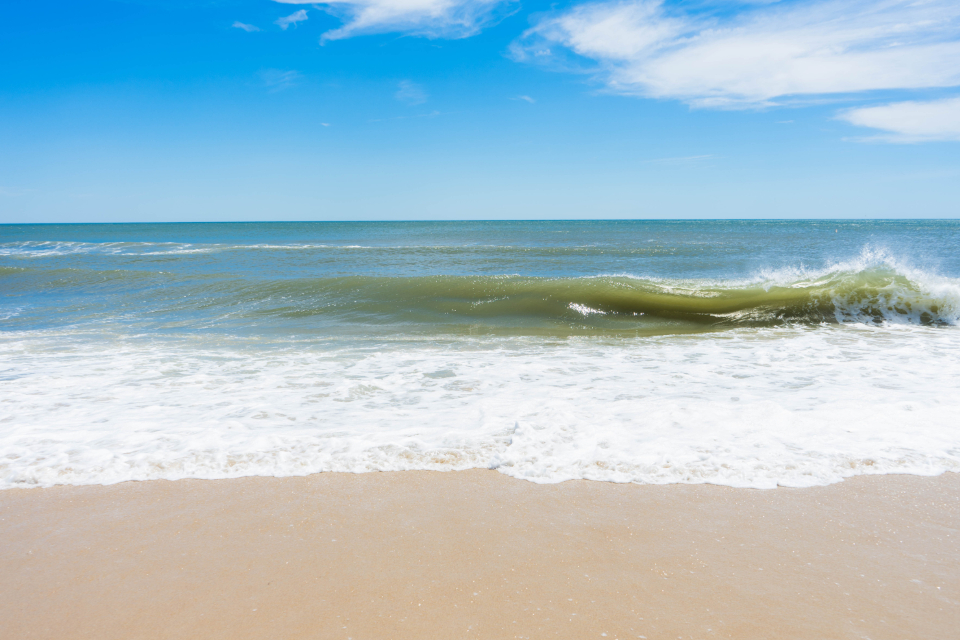 beach sand waves wet ocean saltwater nature shore coast foam water blue tide aqua sky clouds