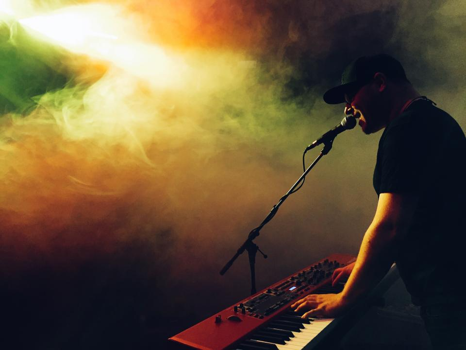 musician singing instrument microphone stage concert smoke entertainment electric keyboard band entertainment guy man people