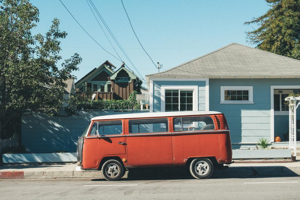 transportation van mini bus red wheels street parking neighborhood residential houses power lines sky trees