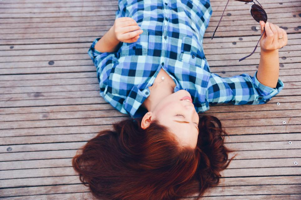 girl woman smile smiling happy people brunette long hair plaid shirt fashion clothes sunglasses wood deck outdoors lying down