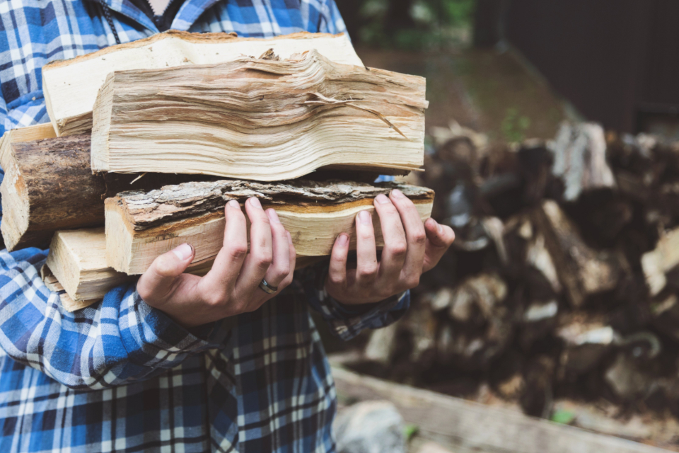 firewood man woodpile flannel shirt lifting lugging hands holding wood walking fingers ring bokeh