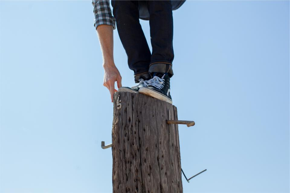 wood post climbing shoes jeans denim hand blue sky