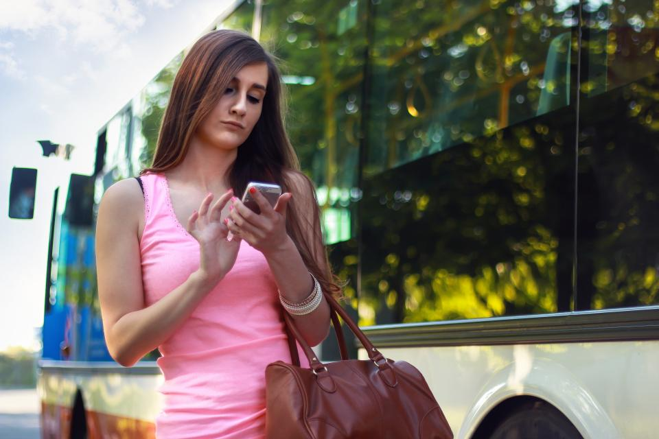 young girl long hair brunette pink tank top cell phone mobile purse bus texting iphone technology