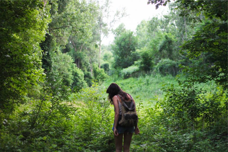 young girl long hair brunette backpack knapsack jean shorts tank top grass trees people nature