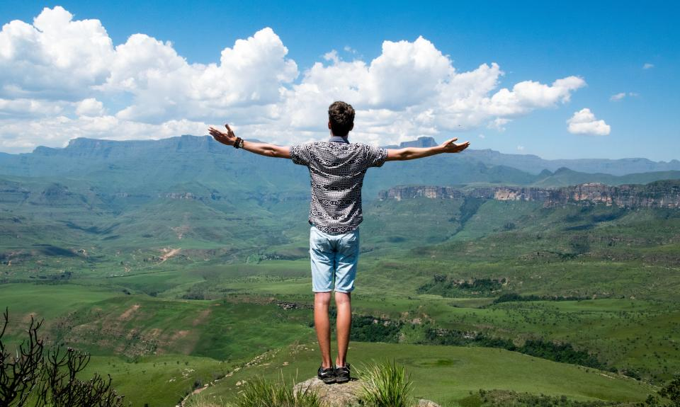 guy man male people back stand arms raised mesmerizing nature landscape mountains summit peaks plains grass bushes sky clouds horizon travel trek hike climb