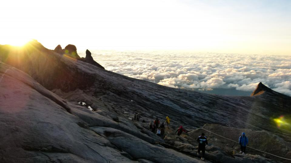 sky clouds sunlight sunset hiking hikers people mountains peaks cliffs trek trail cold jackets
