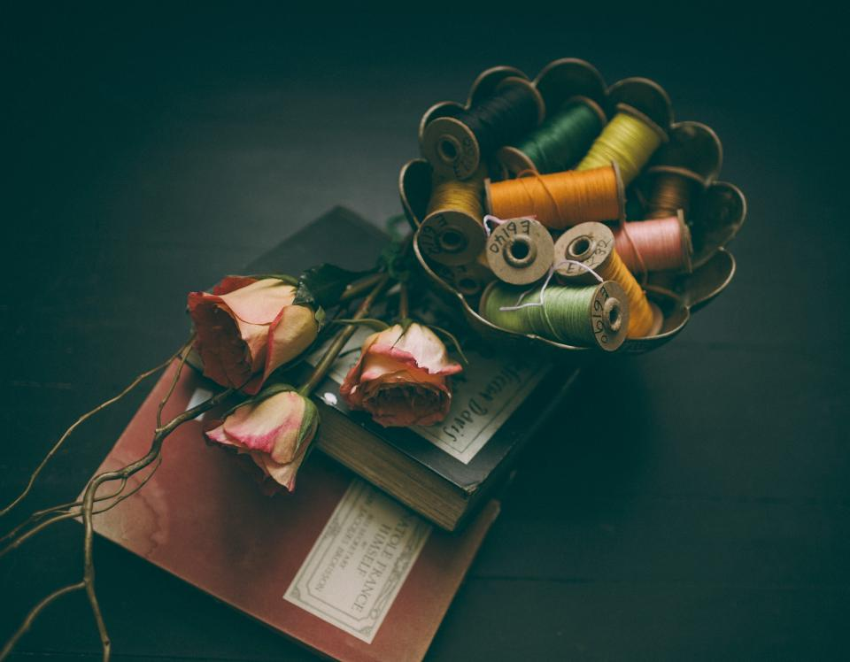 still items things flowers books journals yarn thread bokeh