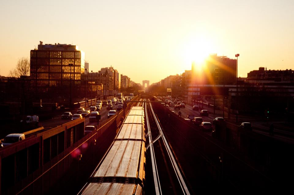 sunset sky buildings train tracks railroad cars trucks highway traffic busy