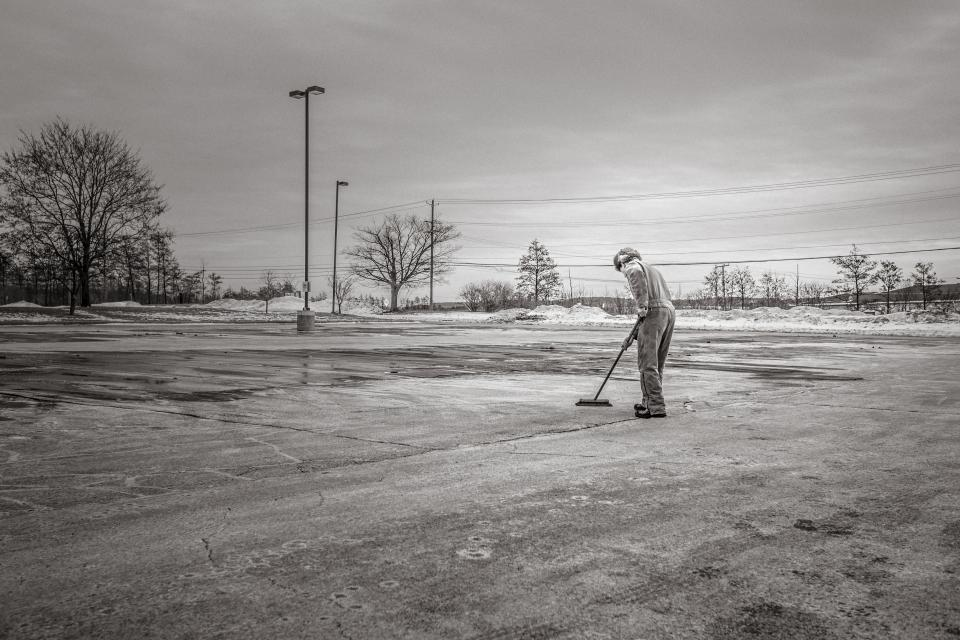 sweeping broom cleaning man concrete lot