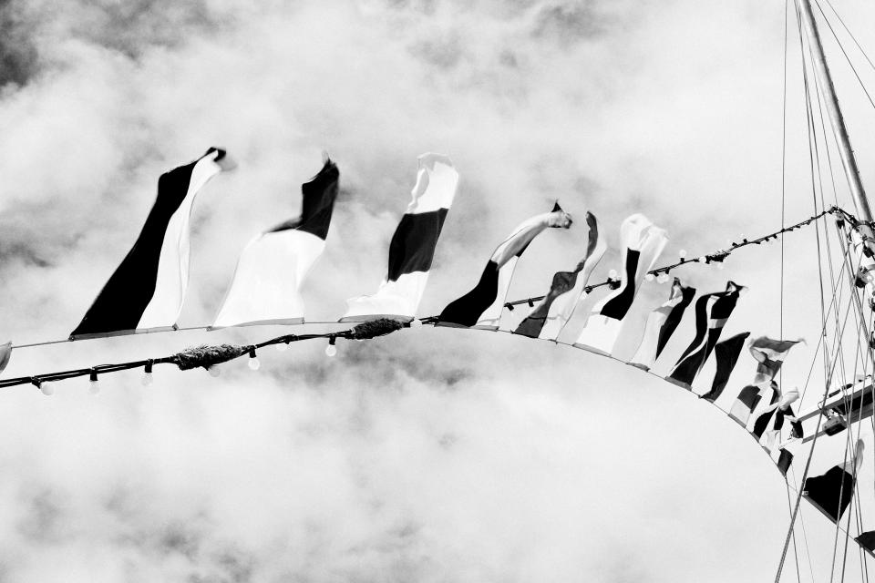 black and white flags string fairy lights ropes sailboat sky clouds