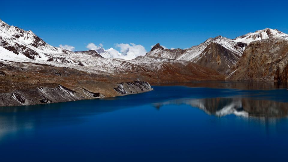 nature landscape mountains snow summit peaks coast water ocean sea lake reflection sky clouds brown blue