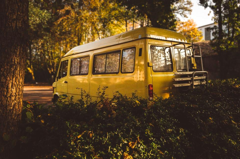 yellow van car vehicle green plants nature trees road