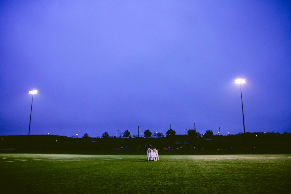 soccer field lights night dark grass athletes fitness sports team people group