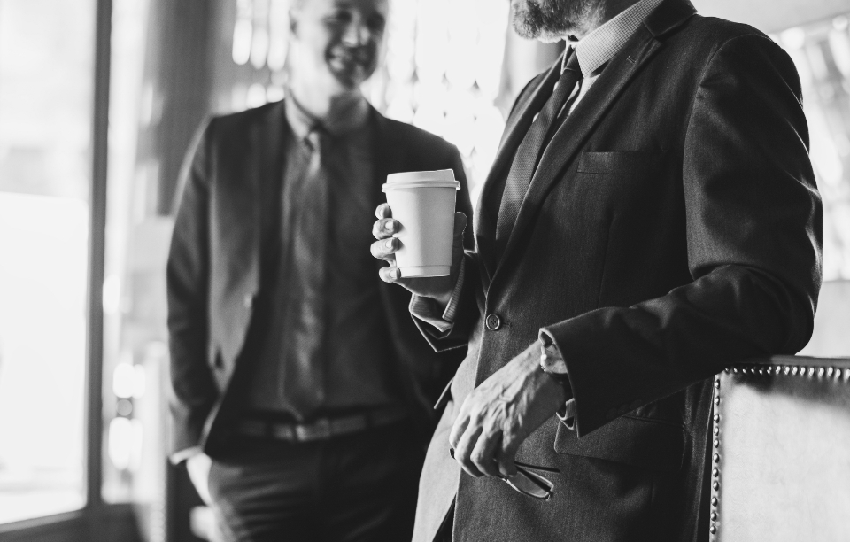 black and white business businessman bw cheerful coffee coffee cup communication cup discussion drink eyeglasses gray scale hands happiness holding meeting men paper cup partner people plan relaxed smiling standing success suit beverage