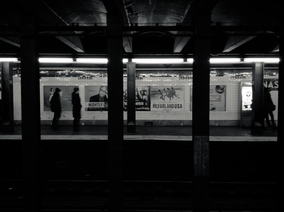 subway station transportation urban black and white NYC New York city platform pillars people