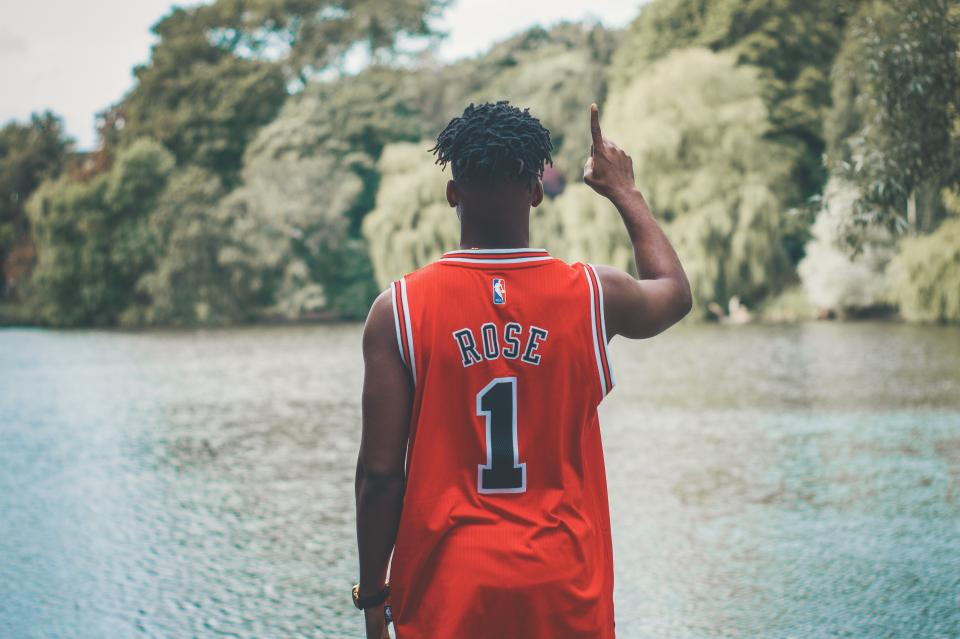 people red jersey basketball player one nature lake water trees plant outdoor blur black african american