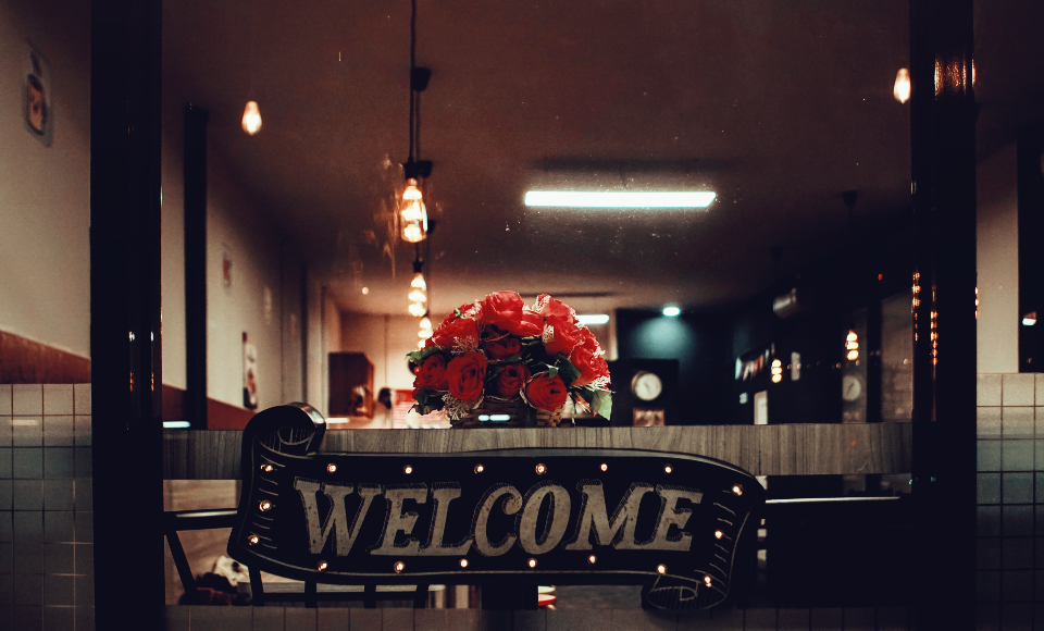 welcome sign vintage rustic wood business coffee shop flower bouquet furniture glass lamp light restaurant signage