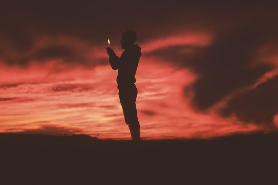 people man fire light silhouette travel adventure sunset clouds sky