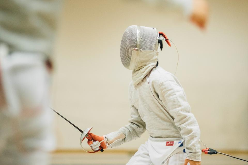 people man teen sport fencing olympic sword gear mask uniform white practice duel fight game play string referee wall gym training