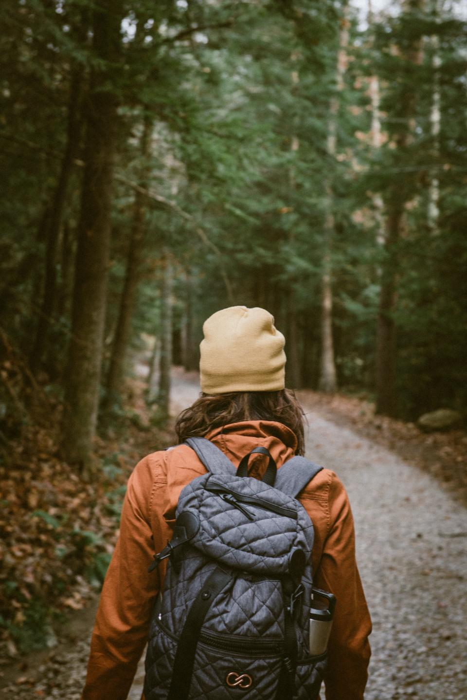 backpack people hiking walking woman beanie path road trees plant forest