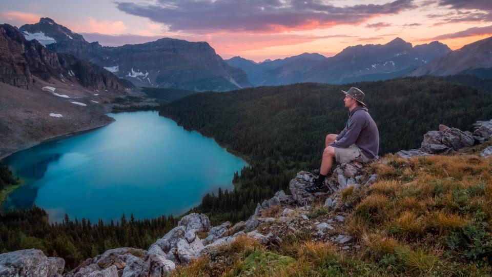 lake blue water green trees plants clouds sky sunset landscape mountain rocks grass highland view nature people man guy sitting alone adventure travel hiking outdoor