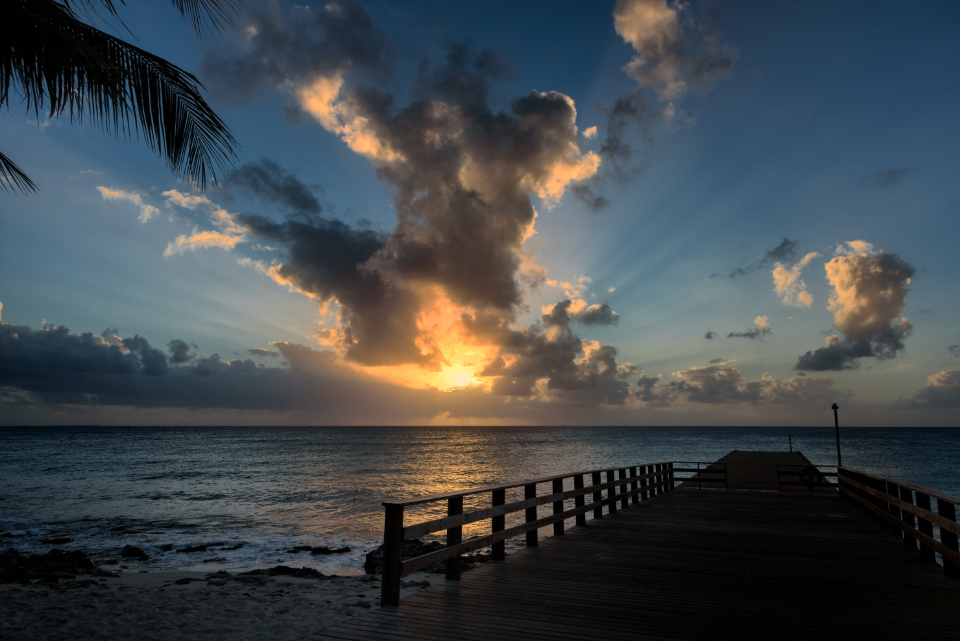 tropical pier sunset water ocean clouds peaceful calming landscape scenic air view blue outdoors sea dock