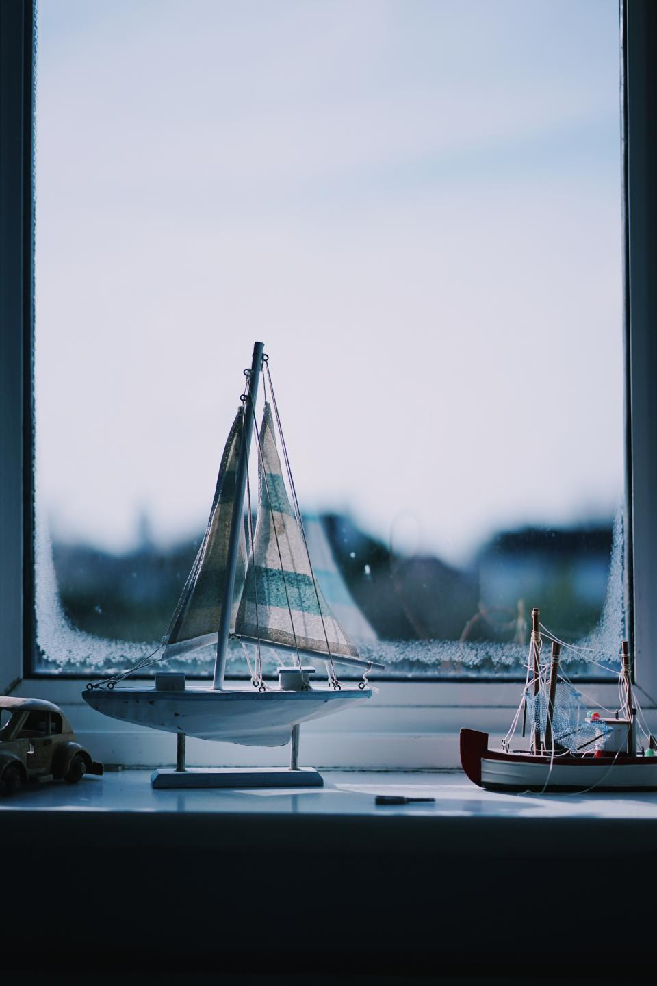 still items things miniature scale model ship sail display collection window pane view bokeh