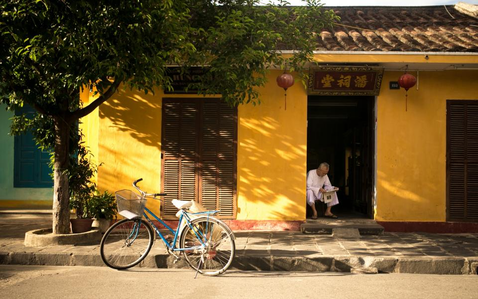 bike bicycle tree stones sidewalk street old man asian yellow house roof