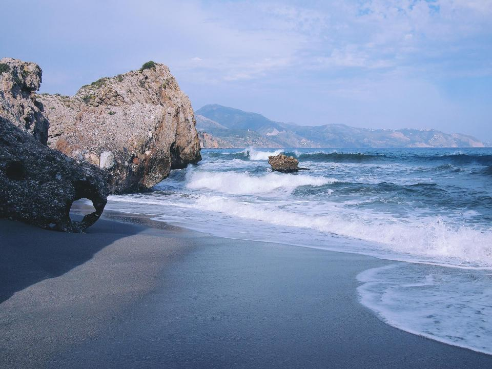 beach sand shore ocean sea waves water rocks boulders sunshine summer Nerja Spain coast