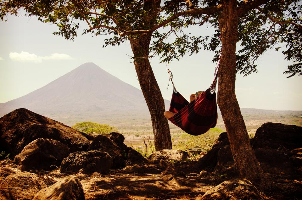 nature landscape mountains summit peak slope grass trees sky clouds view man woman people hammock leisure relax
