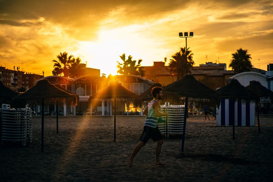 building structure cottage beach sand shore resort hotel vacation people man running sunset sunrise sunlight sky clouds sunshine