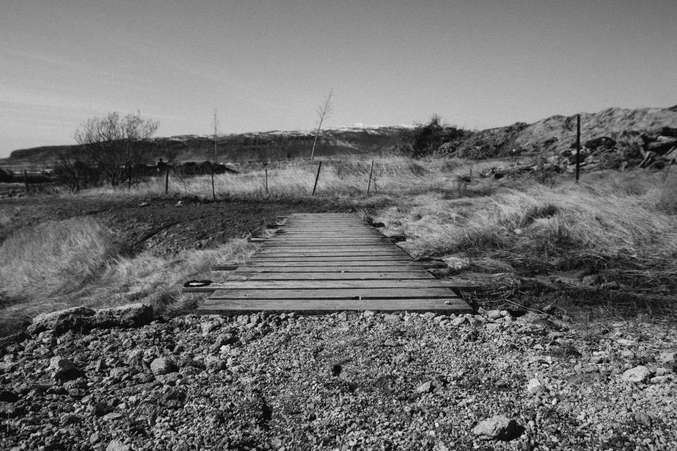 wood bridge rocks dirt fields grass country black and white