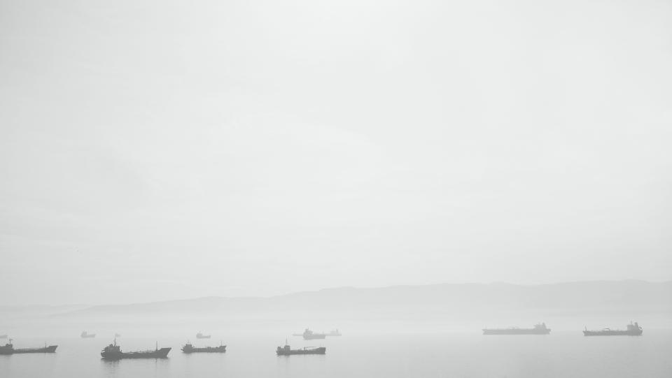 black and white grey sky water boats ships steam fog haze ocean