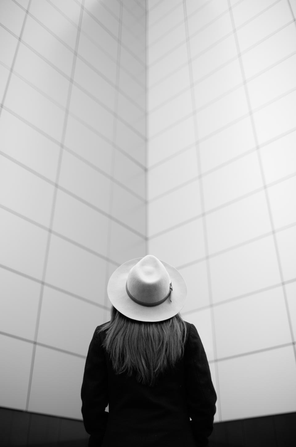 black and white people girl hat alone wall