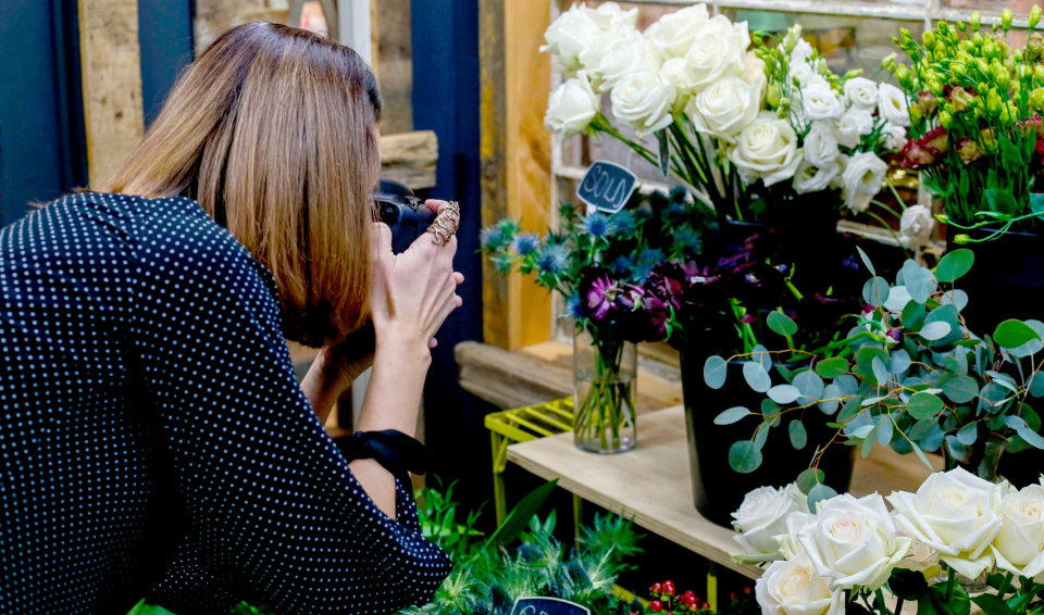 photographer picture photo camera lens working table professional person flowers plants vase woman female