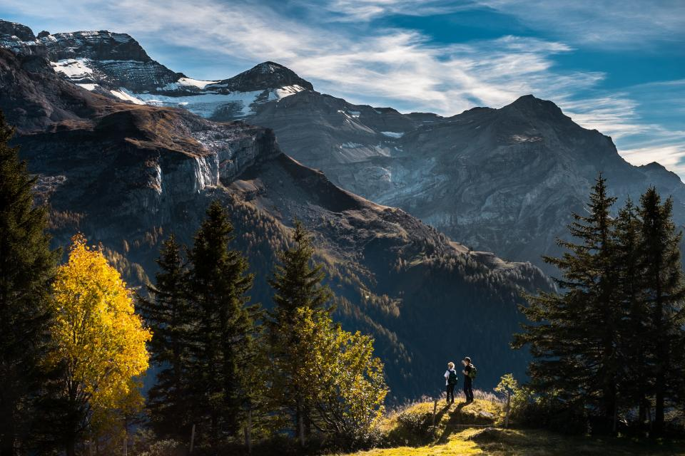 sky clouds mountains peak snow hiking hike trek outdoors nature man woman knapsack backpack trail trees sunlight woods