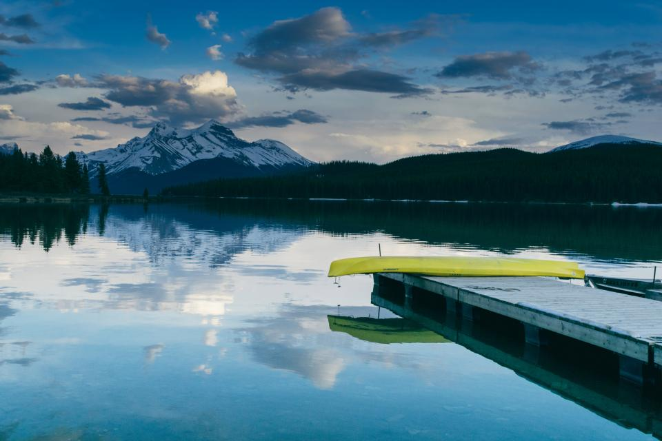 lake water dock canoe reflection landscape nature trees mountains hills sky clouds outdoors cottage