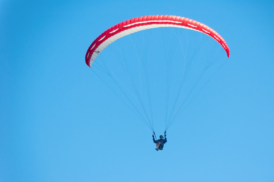 paraglide blue sky fly person athlete sport free light red peace calm adrenaline exciting people