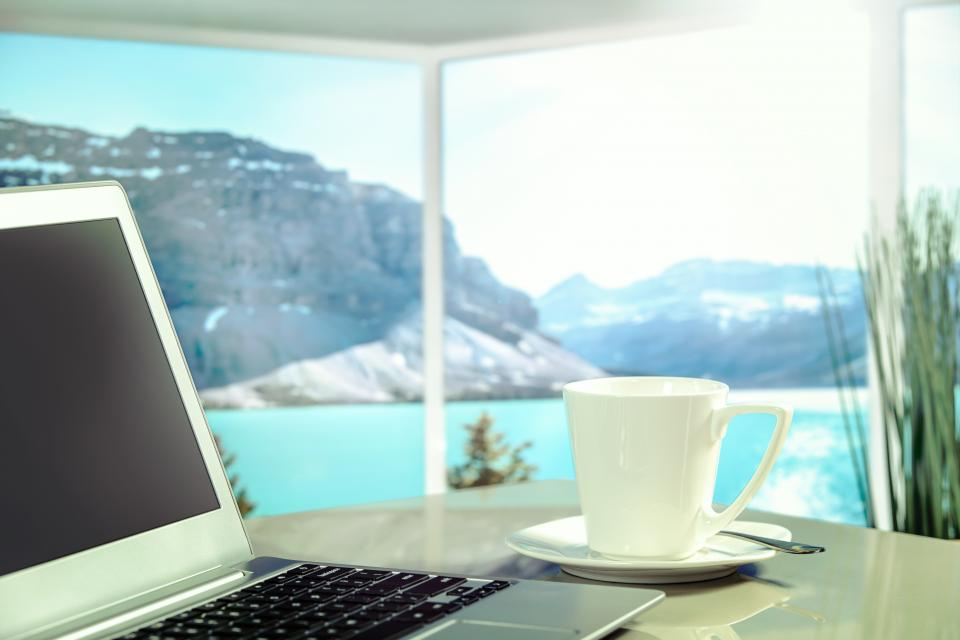 laptop apple macbook computer browser research business travel vacation work table coffee sea blue water mountain view landscape nature