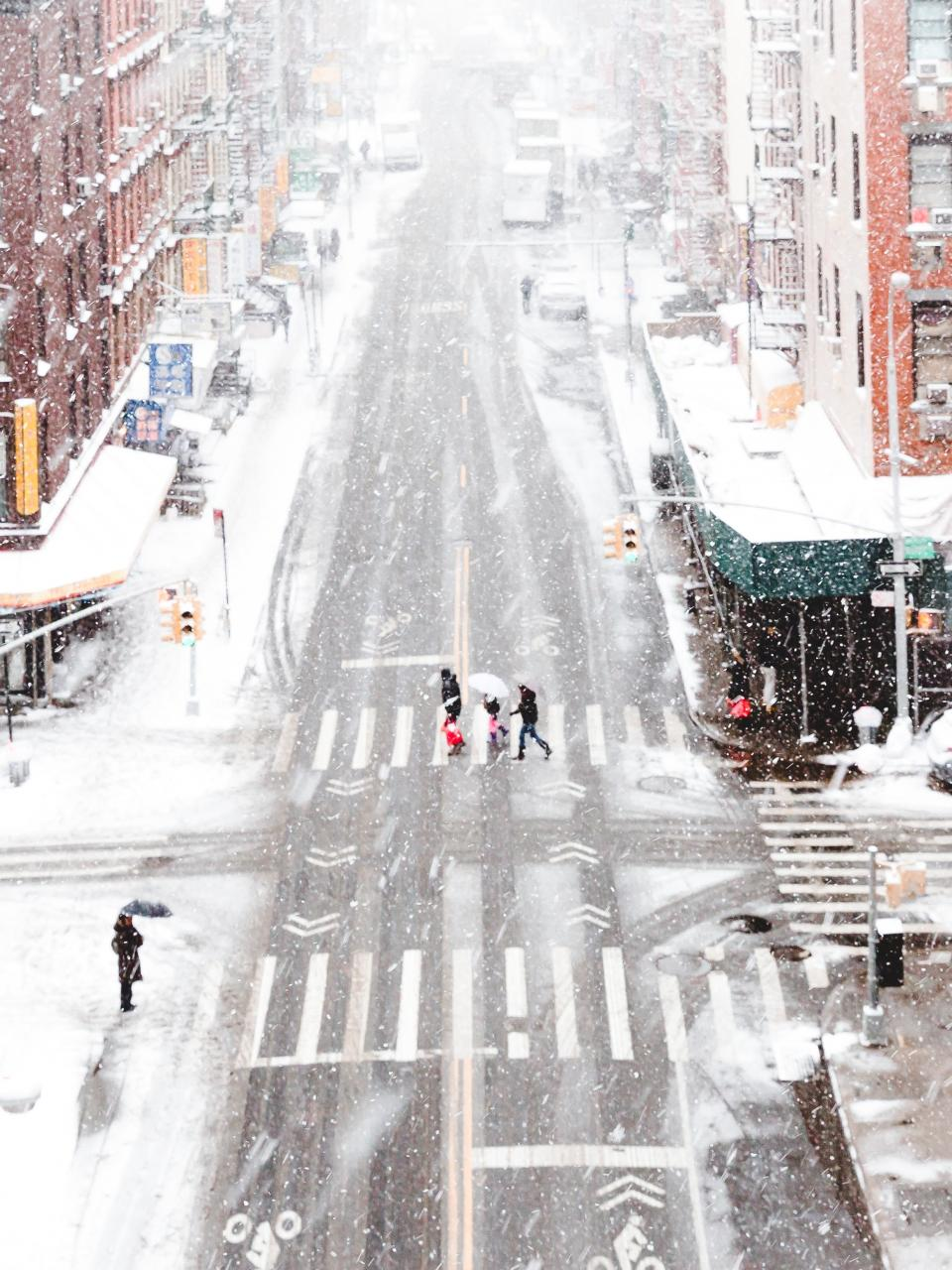 snow city urban people pedestrian lane signs street buildings architecture infrastructure children snowing traffic light intersection
