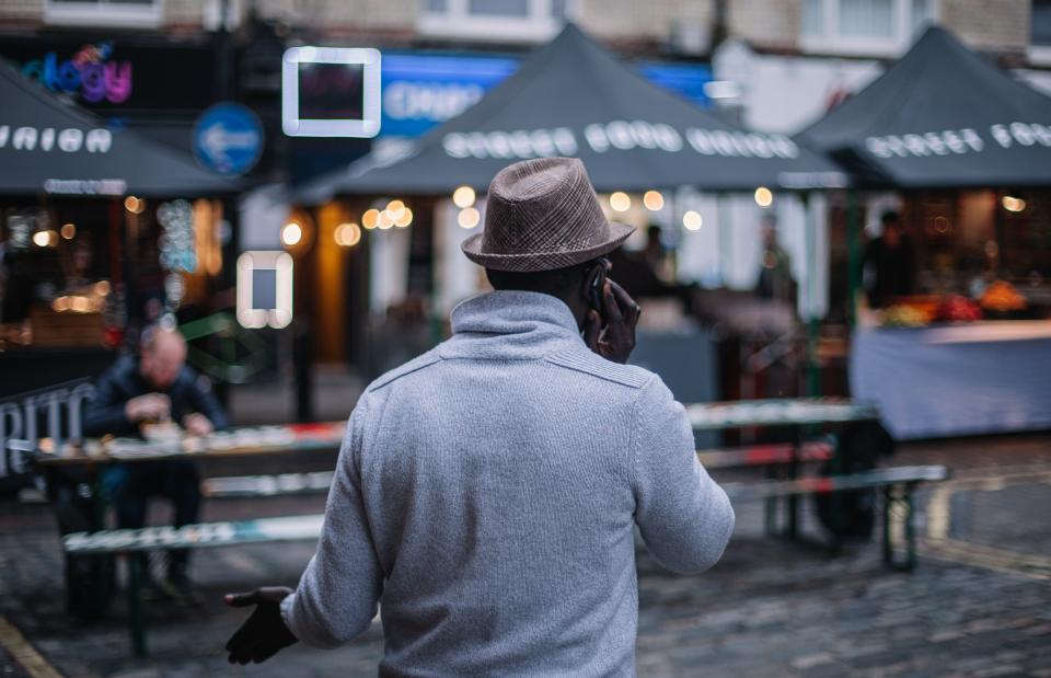 people man male back hat talking mobile phone communication bokeh travel city