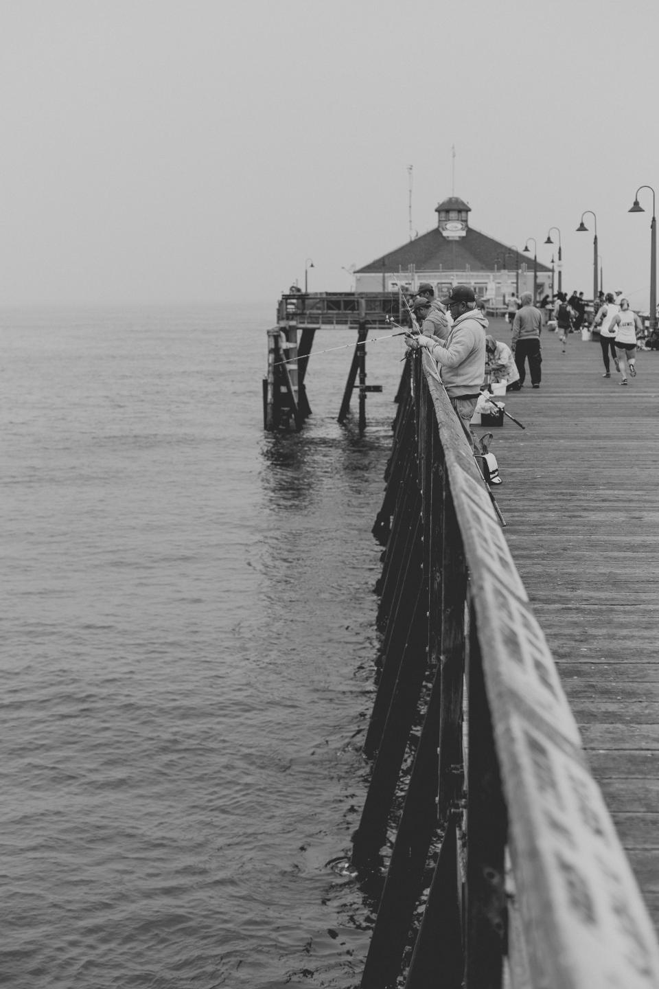 pier pathway ocean sea water people travel fishing black and white