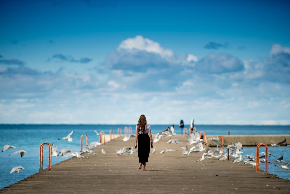people girl walking alone sad bridge birds flying pathway steel ocean sea water nature sky blue clouds