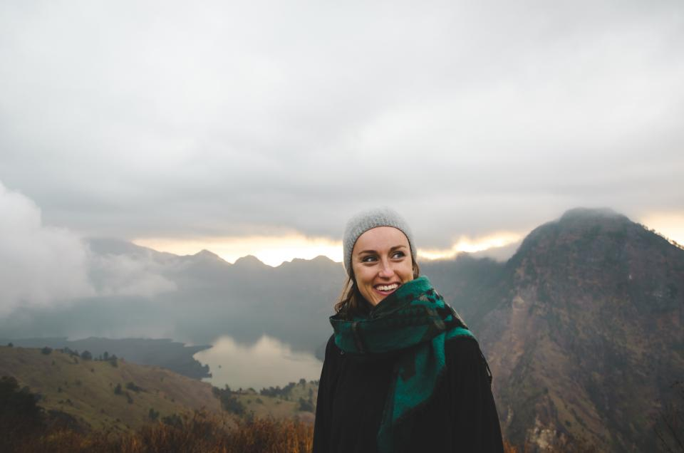 people woman happy scarf mountaineer bonnet mountain travel adventure trek hike clouds sky fog lake trees green grass