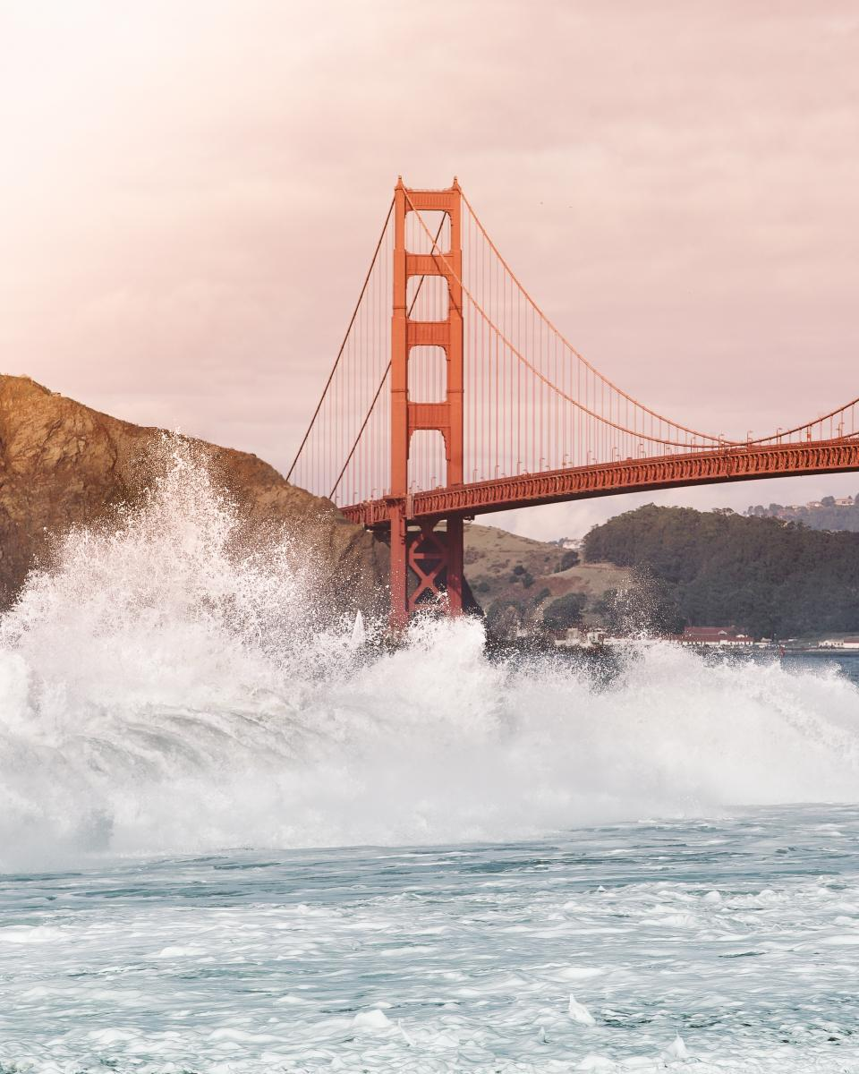 sea ocean water waves nature bridge architecture structure hill sky blue clouds highland mountain