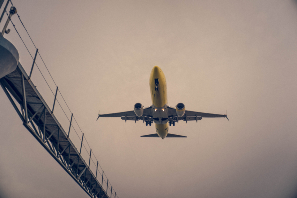 plane flying overhead cloudy sky flight fly transport yellow carrier passenger
