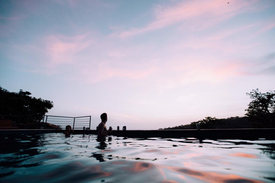 people man girl couple swimming pool water drinks beverage sky dark sunset tree